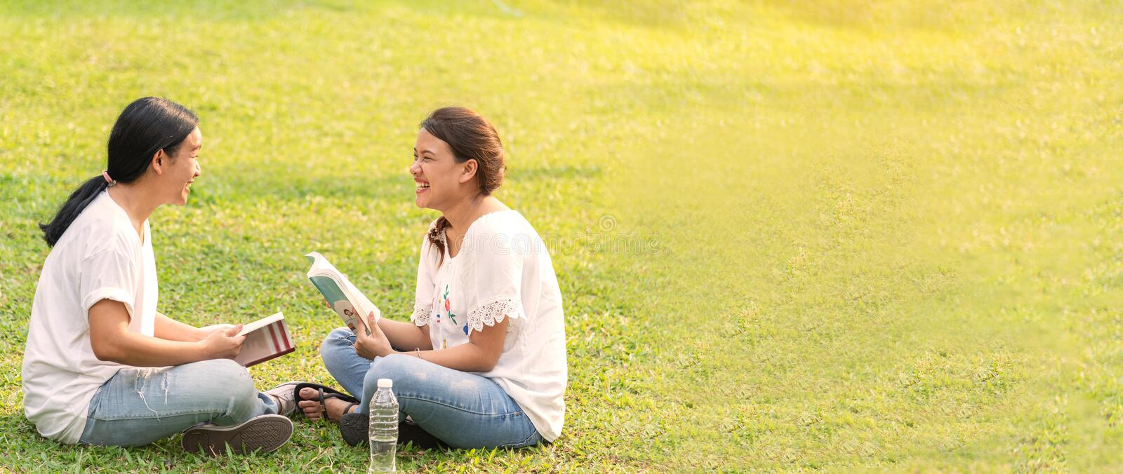 Two young women sitting having a happy time and reading book in the park royalty free stock photos