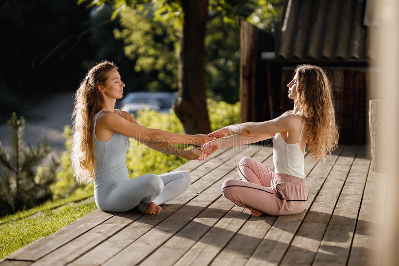 Two young women are sitting and holding hands in the lotus position on a wooden podium in the garden near the house in. The sunny morning stock images