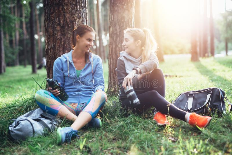 Two young women in sportswear sitting under trees in the forest drinking water, talking and resting after training royalty free stock photo