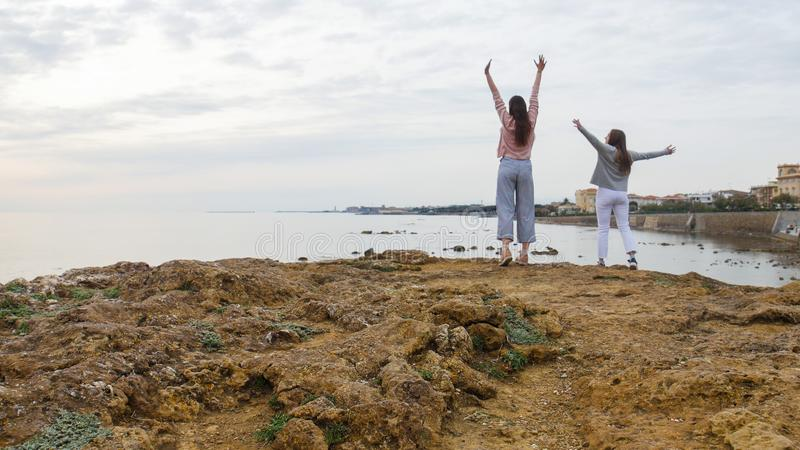 Two young women stand on stones in the sea and put their hands up. Wide angle stock photography