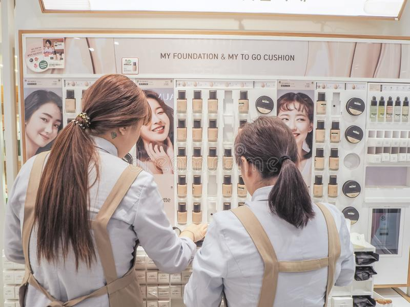 Two young women standing in front of a shelf with Korean cosmetics royalty free stock image