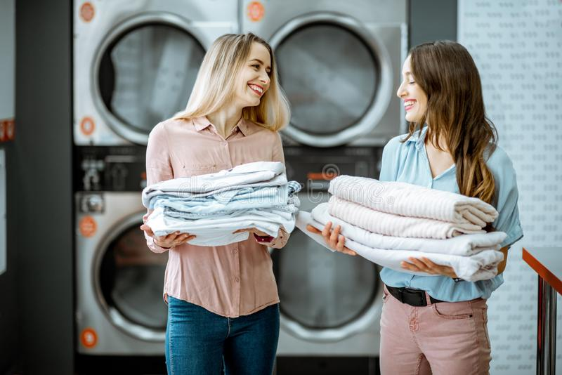Women with clean clothes in the laundry. Two young women standing together with clean clothes in the self serviced laundry with dryer machines on the background stock photos