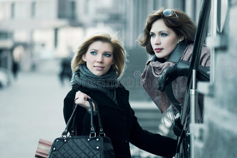 Two young fashion women walking in a city street stock image