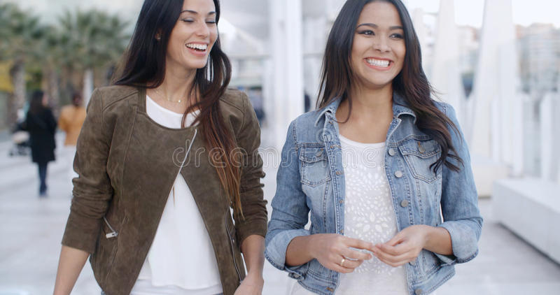 Two young women strolling down a promenade royalty free stock photo