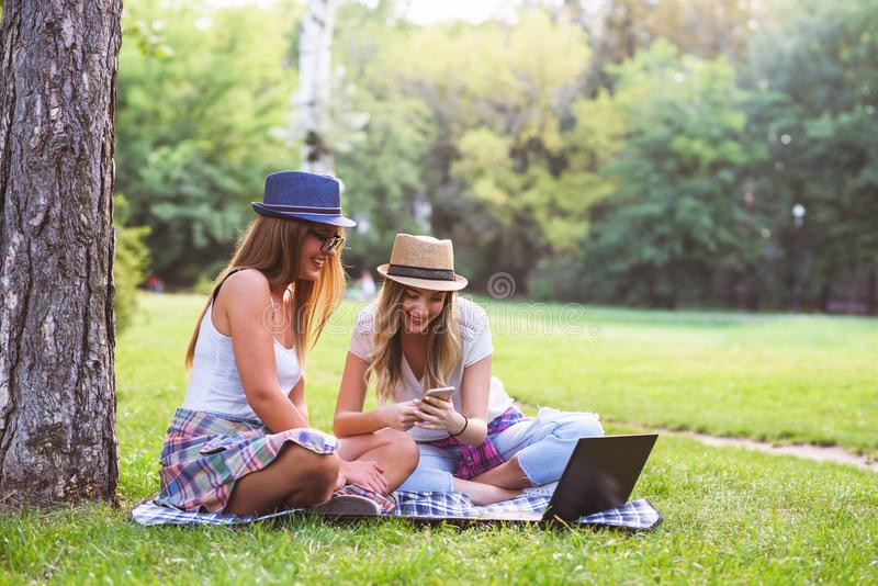 Two young women students in park sitting on grass talking, using laptop royalty free stock image