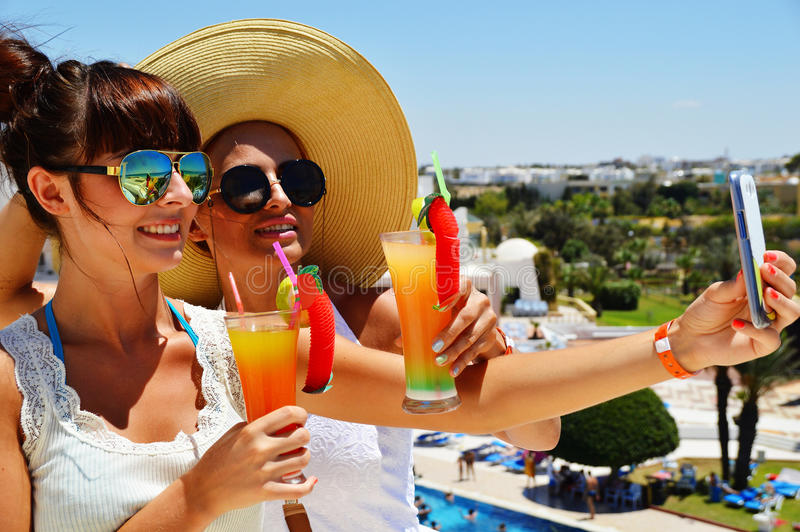 Two young women taking picture of themselves on vacation stock photography