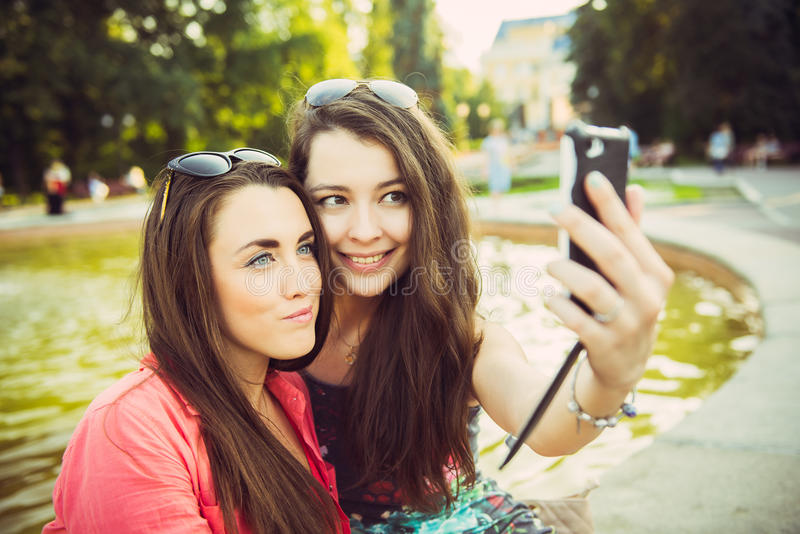 Two young women taking a selfie outdoors stock photography