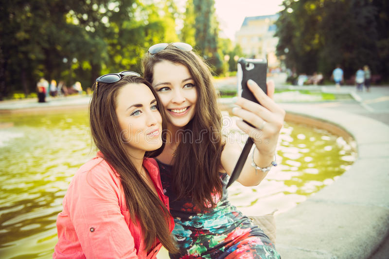 Two young women taking a selfie outdoors royalty free stock photos