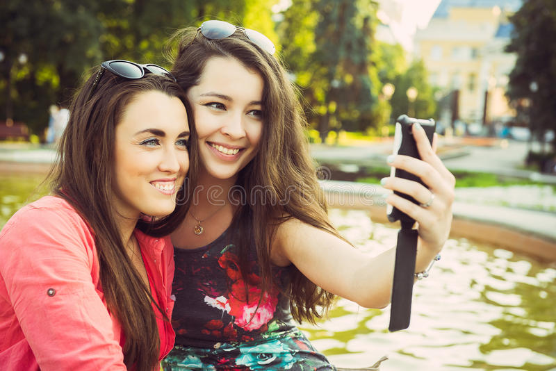 Two young women taking a selfie outdoors stock photo