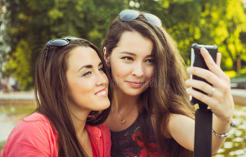Two young women taking a selfie outdoors royalty free stock photography