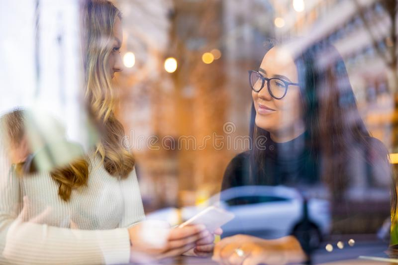 Two Young Women Talking At Cafe in City Seen Through Window stock photos