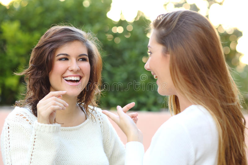 Two young women talking outdoor. Two young women talking happy outdoor royalty free stock images