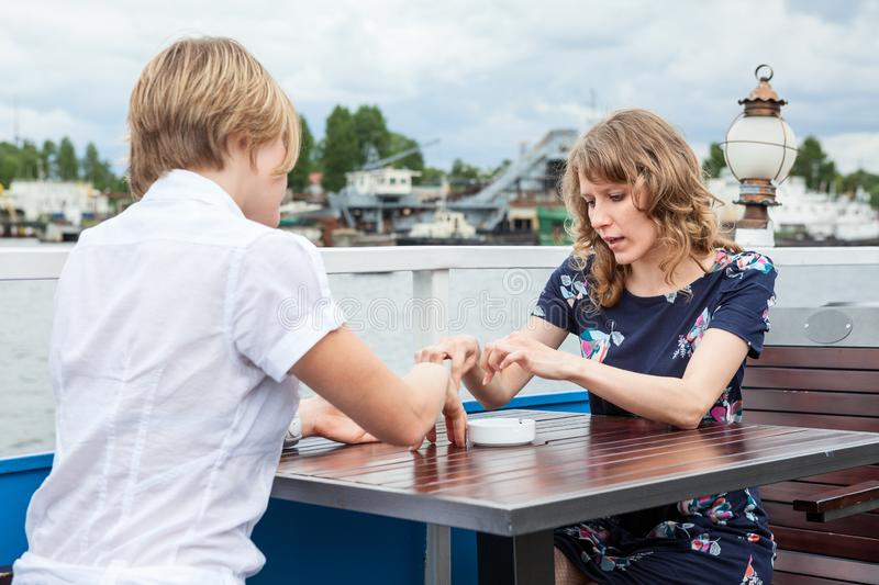 Two young women talking together while sitting at the table in summer cafe stock photography
