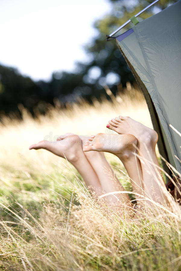 Two young women with their legs sticking out of a tent royalty free stock image