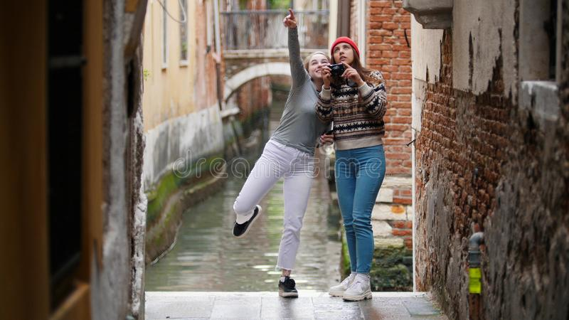 Two young women travelers in warm clothes standing on a background of a water canal and taking photos - Venice, Italy stock images