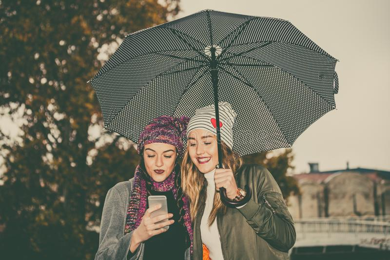 Two young women with umbrella and using mobile phone in the street stock photo