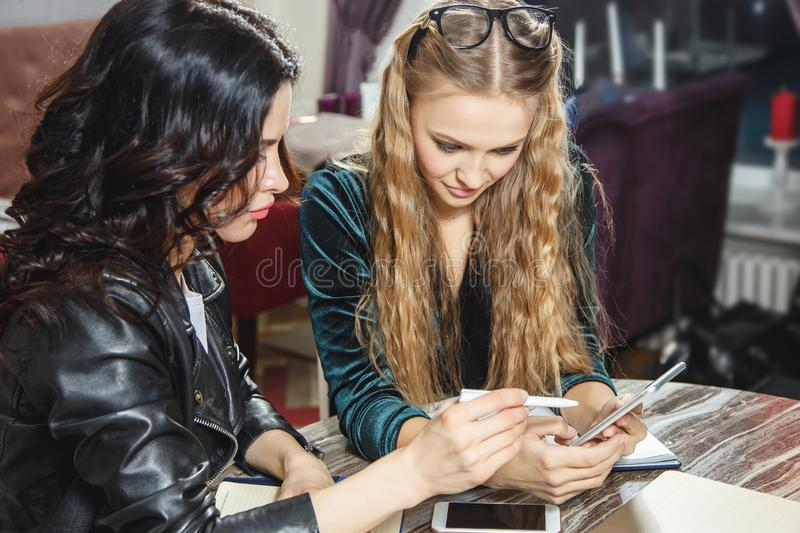Two young women using a smartphone in a cafe. Team work. royalty free stock image