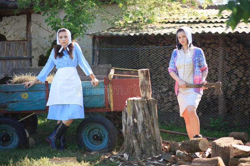 Two young women in the village. Woman holds an ax. Portrait in retro rural style stock images