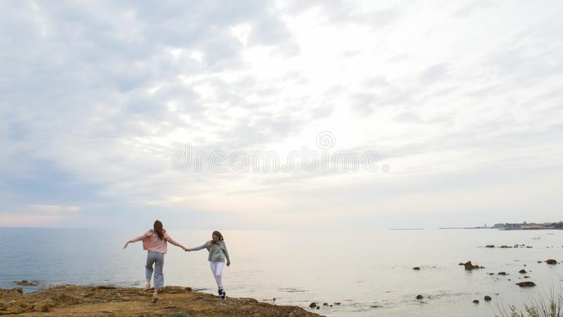 Two young women walking on the rocky shore near the sea and hanging hands. Shot from afar stock images