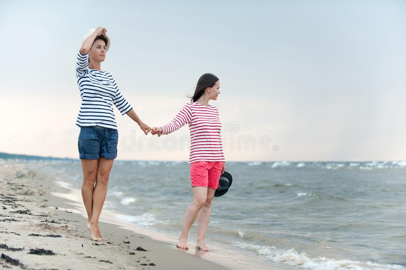 Two young women walking together holding hands on the seaside. Two young women walking together holding hands on stormy seaside. Friends/sisters. Summertime stock photography