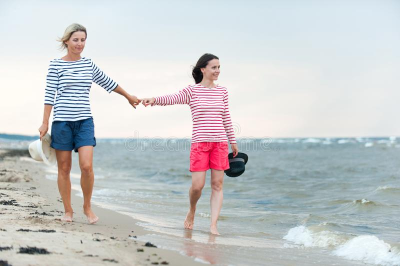 Two young women walking together holding hands on the seaside. Two young women walking together holding hands on stormy seaside. Friends/sisters. Summertime stock photo