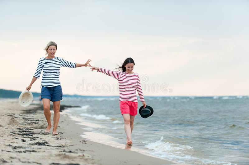 Two young women walking together on the seaside holding hands. Two young women walking together holding hands on stormy seaside. Friends/sisters. Summertime stock images