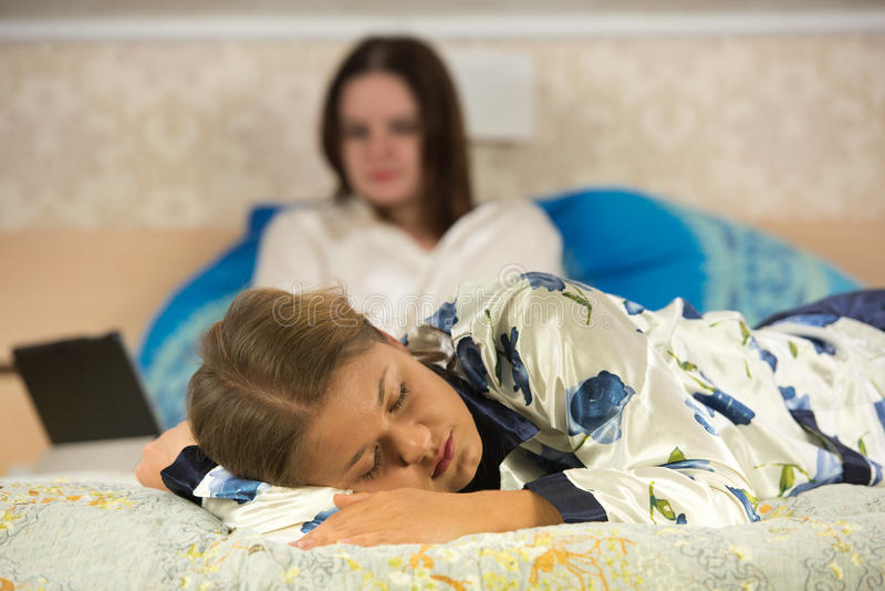 Two young women wearing pajamas in bed royalty free stock photography