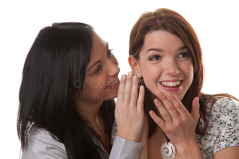 Two young women whisper together