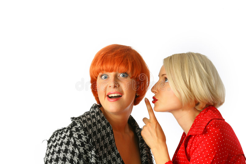 Two young women whispering stock photography
