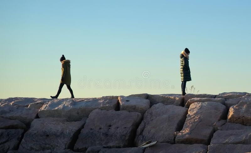 Two young women in winter clothing on boulder walkway. Walking away from each other royalty free stock photos