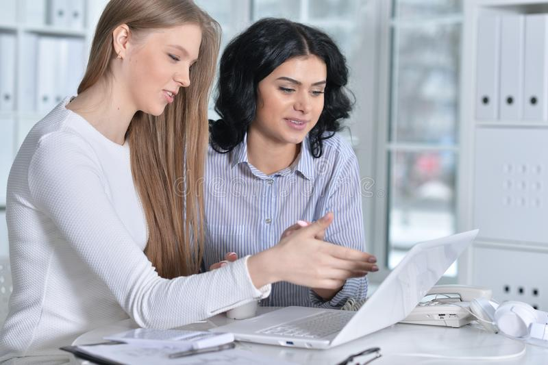 Portrait of two young women working at office with laptop stock images