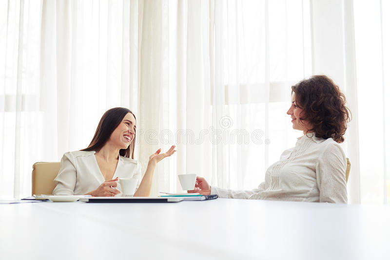 Download Two Young Women Are Working At Team And Drinking Coffee Stock Image - Image of blouse, curly: 70344951