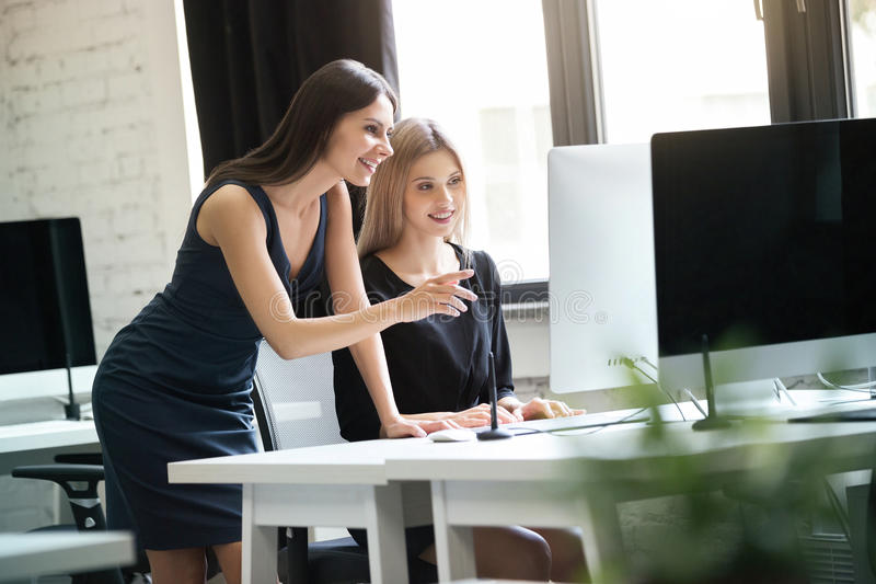 Two young women working together with computer royalty free stock image