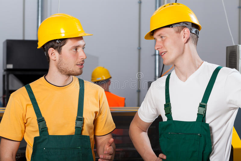Two young workers in production area royalty free stock photo