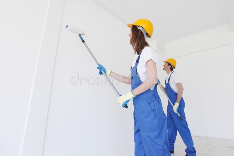 Workers painting the wall. Two young workers in uniform painting the wall royalty free stock photography