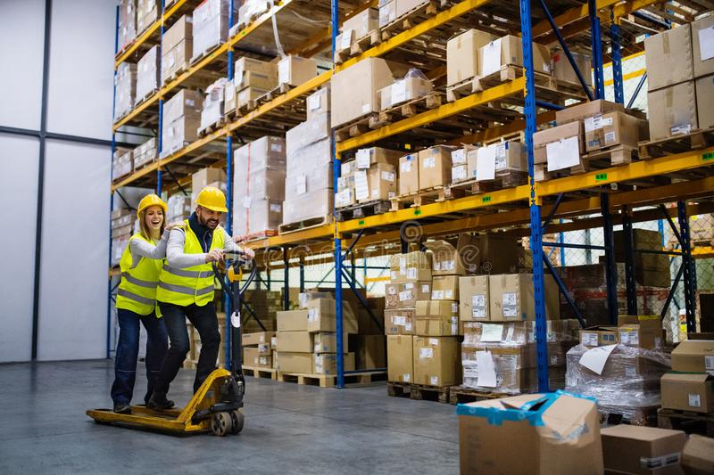 Two young workers in a warehouse. royalty free stock image