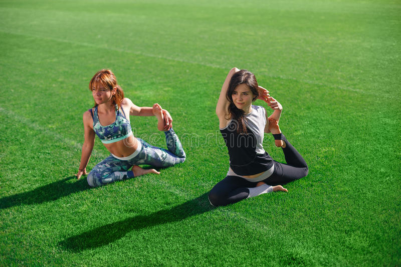 Two young yoga female doing yogatic exericise at the stadium. royalty free stock photos