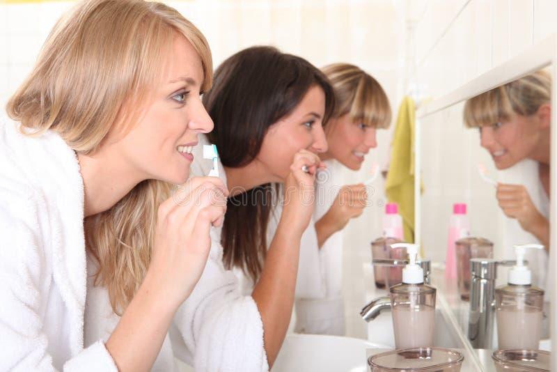 Twomen brushing their teeth stock photos