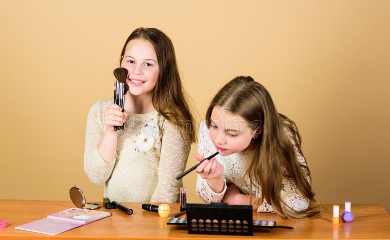 Tworzyć ich styl z dekoracyjnymi kosmetykami Małe dziewczynki stosuje kosmetyki z makeup muśnięciami ma?e dzieci fotografia stock