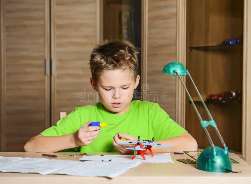 Tworzyć wzorcowego samolot Szczęśliwa chłopiec robi samolotowi modelować Hobby pojęcie zdjęcia stock