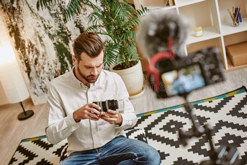 Tworzyć zawartość Młody brodaty blogger mienia kamery obiektyw podczas gdy nagrywający nowego wideo epizod dla jego vlog obrazy stock