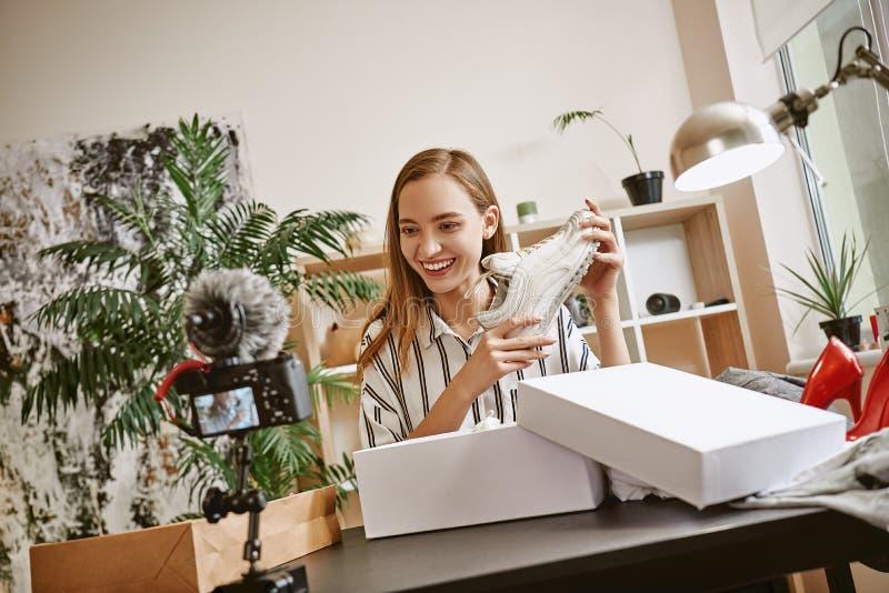Tworzyć zawartość Piękny żeński mody blogger opowiada modnych białych sneakers podczas gdy robić wideo dla jej bloga zdjęcie royalty free