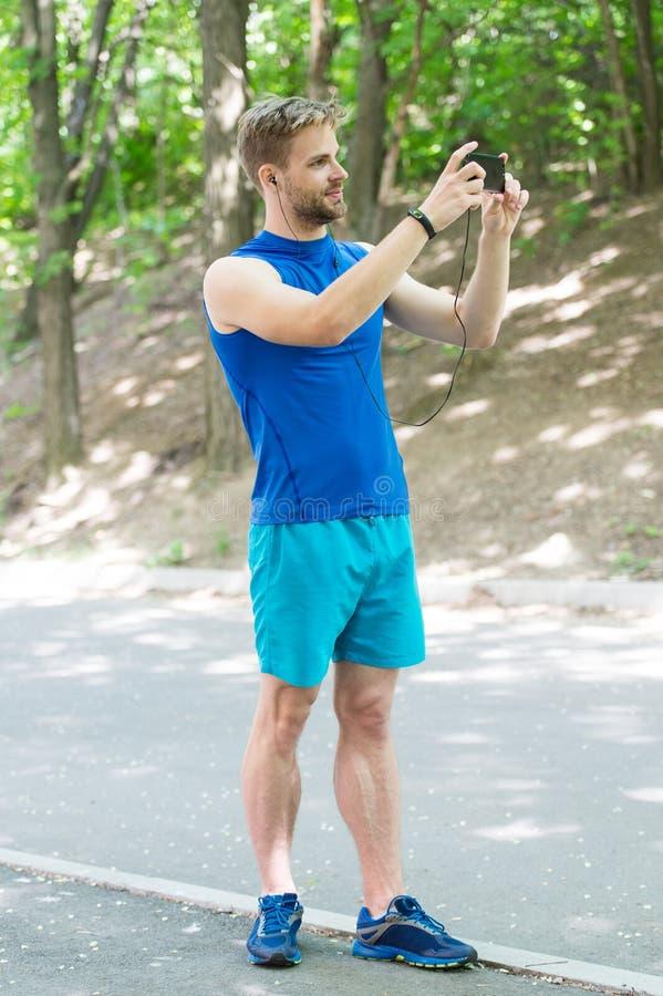 Tworzy trasę biegającą używać zastosowanie Mężczyzny smartphone gotowy zaczynać jog Ustawiania zastosowanie Sportowiec z smartpho zdjęcia royalty free