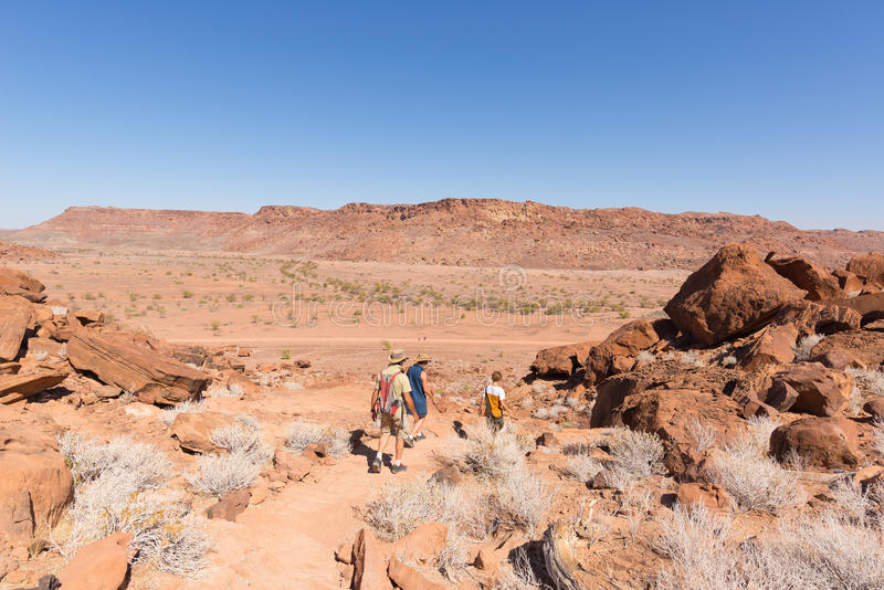 Twyfelfontein, Namibia - August 27, 2016: Group of tourists walking in the desert at Twyfelfontein, world heritage rock engravings stock image