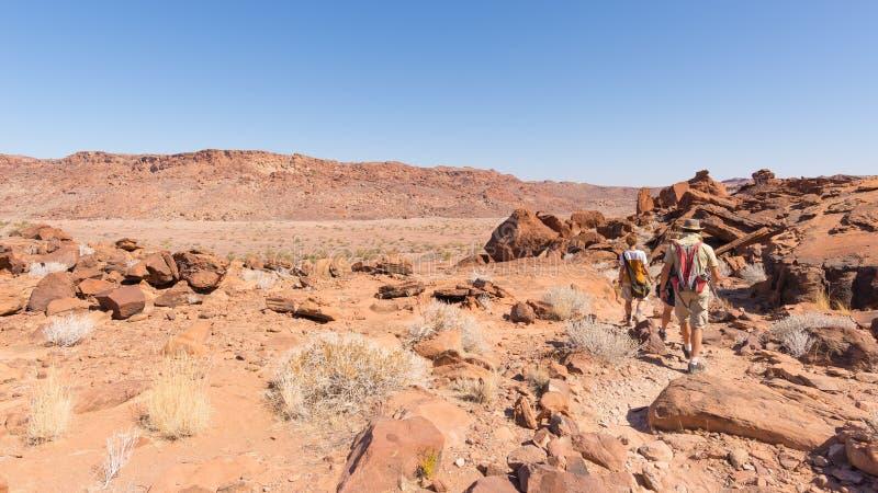 Twyfelfontein, Namibia - 27 de agosto de 2016: Grupo de turistas que caminan en el desierto en Twyfelfontein, grabados de la roca fotografía de archivo