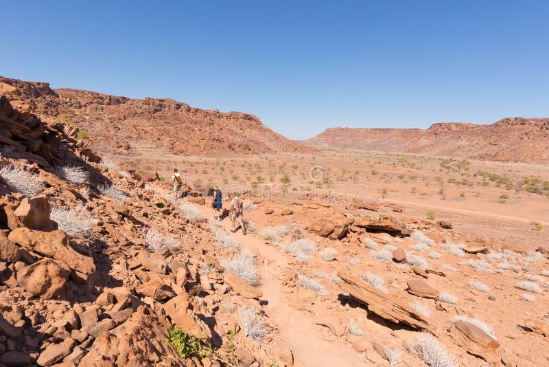 Twyfelfontein, Namibie - 27 août 2016 : Groupe de touristes marchant dans le désert chez Twyfelfontein, gravures de roche de patr photos libres de droits