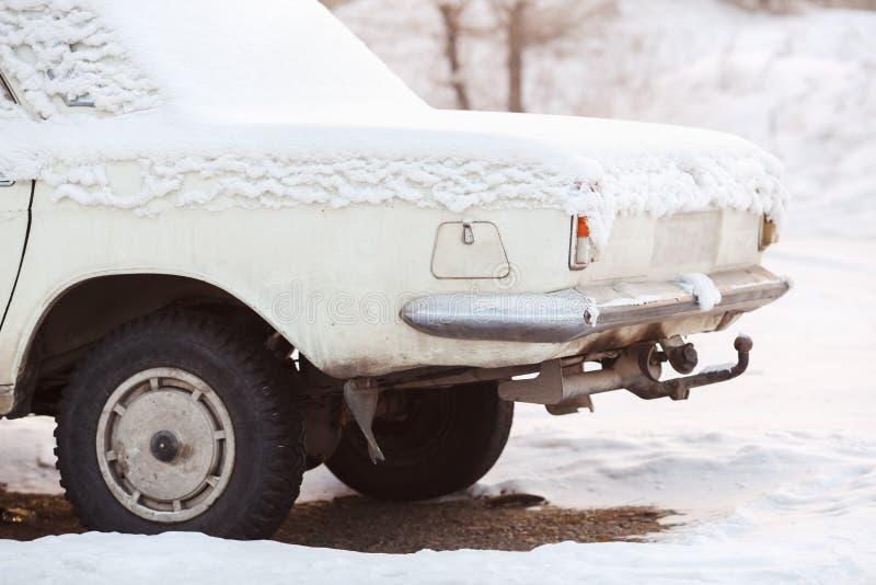 Tyły zakrywający z śniegiem w zimie samochodowy bagażnik, stary łamający biały kolor przy zmierzchem Przetwarzający, metalu przer zdjęcia royalty free