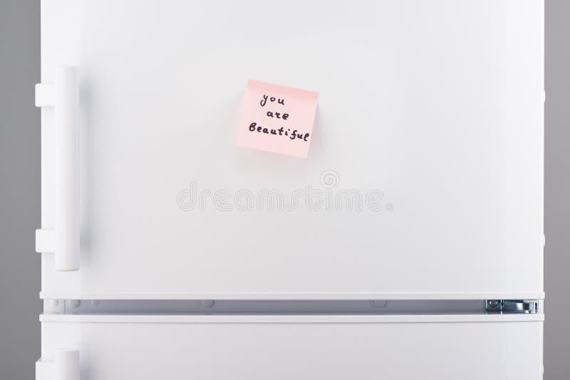 Ty jesteś pięknym notatką na menchia papierze na białej chłodziarce zdjęcie stock