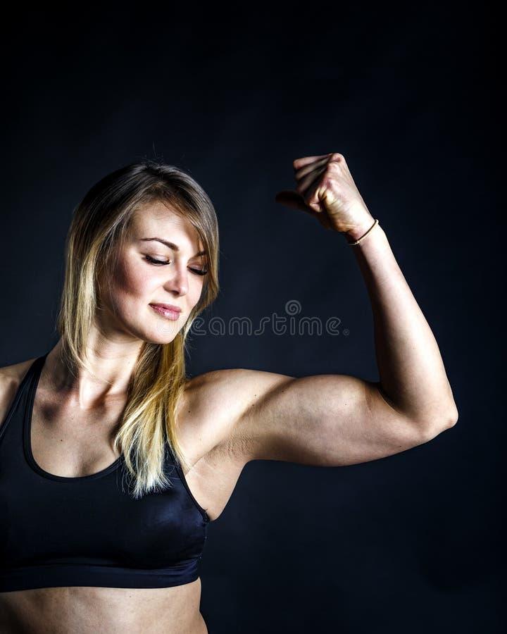 Ty możesz mówić jest hardworker Strzelający sporty żeńska blondynki dziewczyna pokazuje daleko jej perfect ciało na czarnym tle obraz royalty free