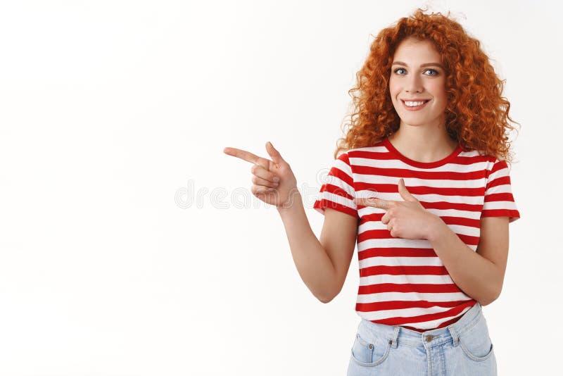 Ty musisz ono widzieć Atrakcyjna elegancka kędzierzawa rudzielec dziewczyna wskazuje lewy palców wskazujących zapraszać uczestnic fotografia royalty free
